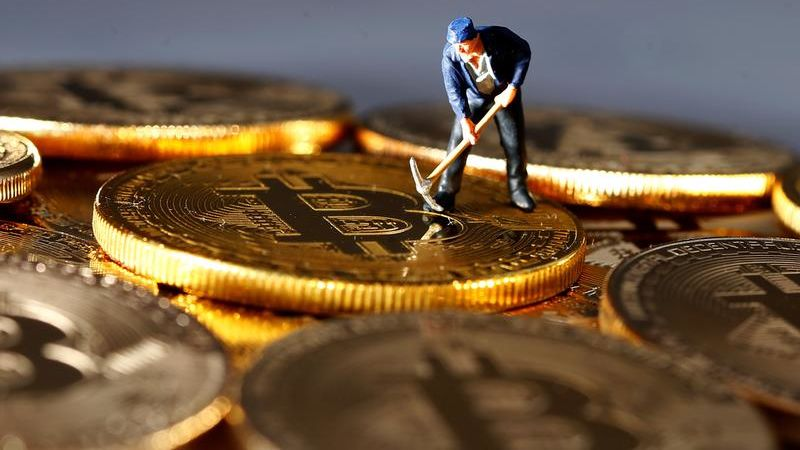 A small toy figure is seen on representations of the Bitcoin virtual currency